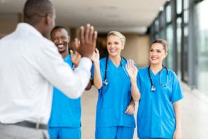 54874903 - rear view of patient waving goodbye to friendly medical team